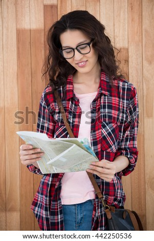 Hipster reading the map on wooden background