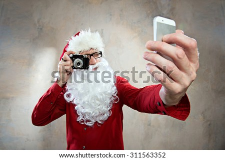 hipster santa makes selfy with retro camera and smartphone - stock photo