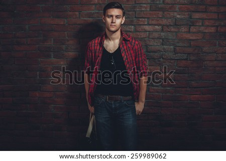 Hipster serious man casual clothes unbuttoned shirt and denim jeans standing near brick wall hand in the pocket looking at camera. - stock photo