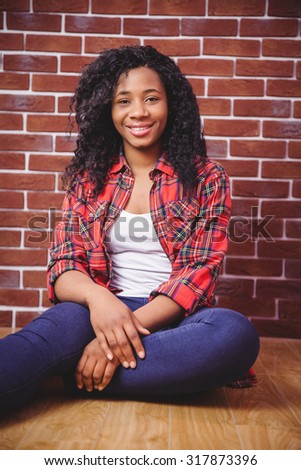 Hipster smiling at the camera on red brick background