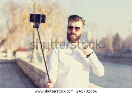 Hipster style bearded man taking selfie with selfie stick. - stock photo