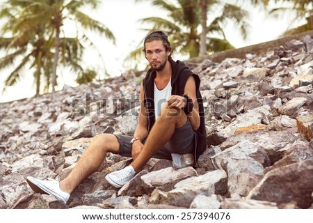 Hipster style boy. Fashion man sitting among the gray stone, palm background - stock photo