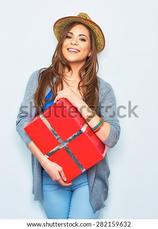 Hipster style young woman holding red gift box. Toothy smile. Positive emotion of female young model. - stock photo