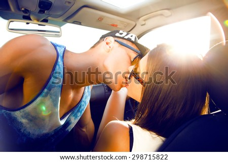 Hipster teen couple looking into each other's eyes and kissing.Sunshine portrait,couple sitting on hood of their car enjoying the moment,outdoors,couple on glasses.Young couple in love on a road trip  - stock photo