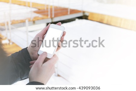 Hipster texting message on smartphone or technology, mock up of blank. Girl using phone on winter snow background close. Tourist female hands holding gadget on blurred backdrop. Mockup side view - stock photo
