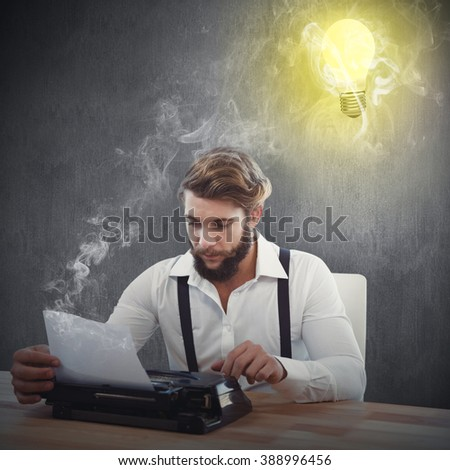 Hipster using typewriter at desk in office against white and grey background