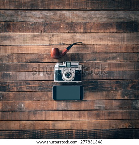 Hipster vintage accessories on an old wooden table, pipe, camera and touch screen smart phone, top view - stock photo