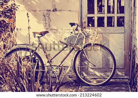 Hipster vintage  Bicycle leaning against grungy wall - stock photo
