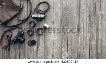 Hipster vintage photography equipment on a wooden desktop with copyspace, top view - stock photo