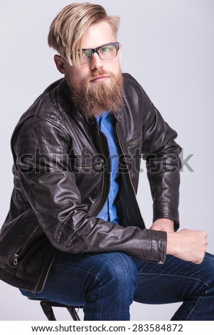 Hipster youn man smiling at the camera while sitting on a chair. - stock photo