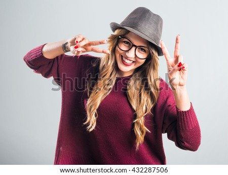 Hipster young girl doing victory gesture - stock photo