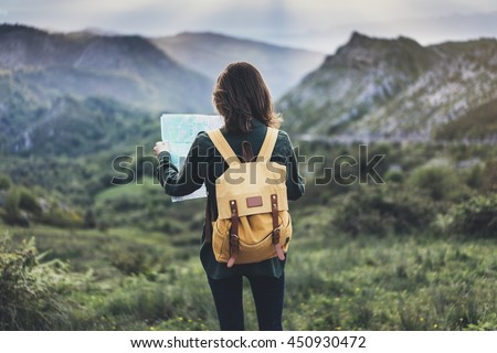 Hipster young girl with  backpack enjoying sunset on peak of mountain, looking map. Tourist traveler on background valley landscape  view mockup, sunlight in trip in  basque country, mock up for text.
