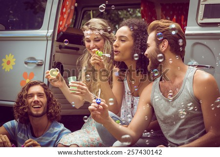 Hipsters blowing bubbles in camper van on a summers day - stock photo