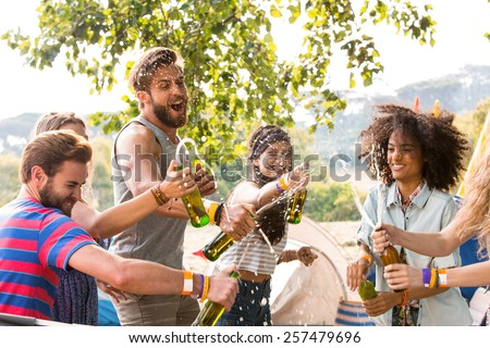 Hipsters spraying beer over each other on a sunny day - stock photo