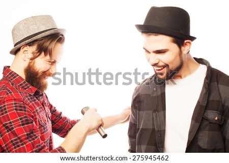 Hipsters: two young mens singing with microphone. Isolated on white. - stock photo