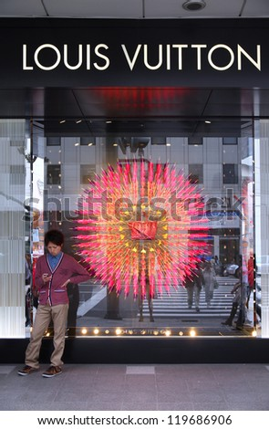 HIROSHIMA, JAPAN - APRIL 21: Shopper stands in front of Louis Vuitton store on April 21, 2012 in Hiroshima. Louis Vouitton was most powerful luxury brand in world with $19.4bn USD value (Forbes 2008). - stock photo