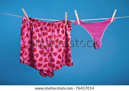 his and her pink underwear on a clothesline - stock photo