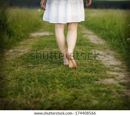 His bare feet beautiful woman close up are on a rural road. - stock photo