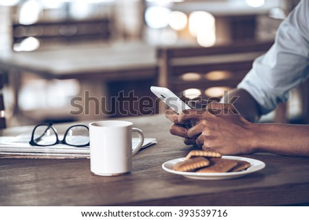 His essentials. Close up part of young African man using his smartphone while sitting at wooden table in caf�©   - stock photo