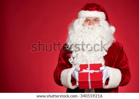 His gift to you. Cheerful and kind Santa Claus holding out a red gift box and smiling happily - stock photo