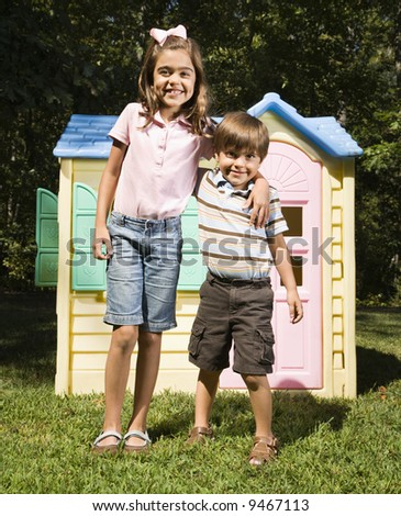 Hispanic boy and girl in front of outdoor playhouse smiling at viewer. - stock photo