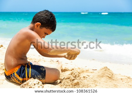 Hispanic boy building a sand castle at a beautiful tropical beach  in Cuba - stock photo