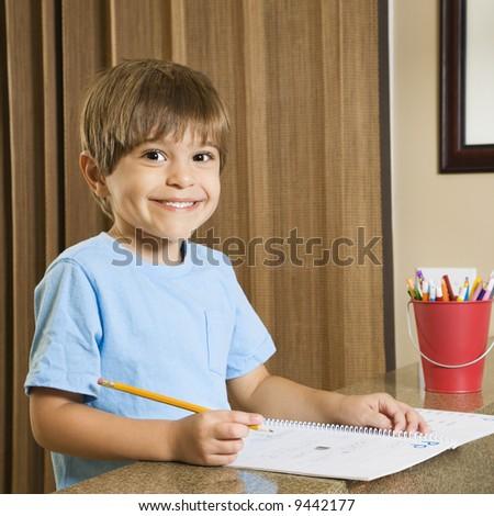 Hispanic boy smiling at viewer and doing homework. - stock photo