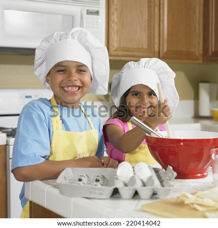 Hispanic brother and sister baking in kitchen - stock photo