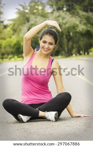 Hispanic brunette in yoga clothing facing camera sitting with legs crossed and stretching right arm above head smiling. - stock photo