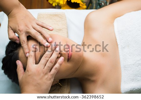 Hispanic brunette model getting massage spa treatment, hands covering womans face