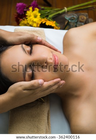 Hispanic brunette model getting massage spa treatment, hands working on massaging womans head and face with eyes closed