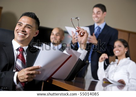 Hispanic business people in boardroom smiling watching presentation, focus on man in foreground
