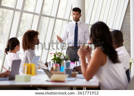 Hispanic Businessman Leading Meeting At Boardroom Table - stock photo