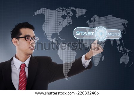 Hispanic businessman pushing a start button to start future 2015 on a virtual screen - stock photo