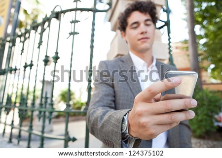 Hispanic businessman using a smart phone while standing in the corner of a classic city street with a green iron rail behind him.