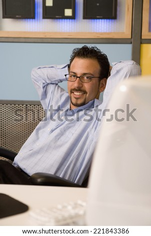 Hispanic businessman with hands behind head - stock photo