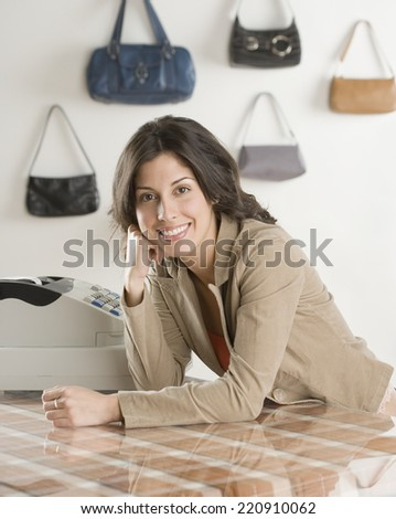 Hispanic businesswoman behind counter at boutique - stock photo