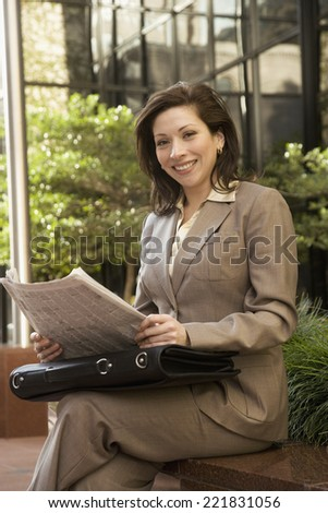 Hispanic businesswoman holding newspaper