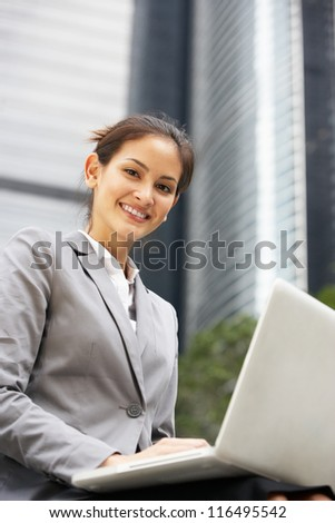 Hispanic Businesswoman Working On Laptop Outside Office - stock photo