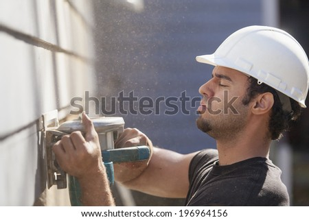 Hispanic carpenter trimming house siding during renovations to add a deck - stock photo