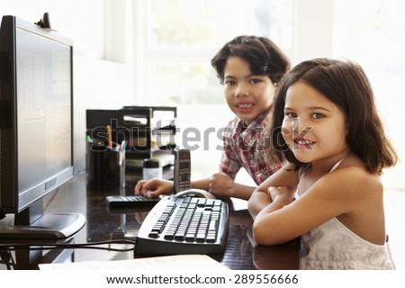 Hispanic children using computer at home - stock photo