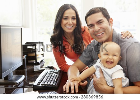 Hispanic couple and baby in home office - stock photo