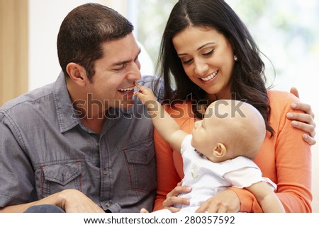 Hispanic couple at home with baby - stock photo
