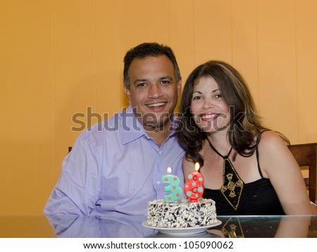 Hispanic couple happily celebrating a birthday - stock photo
