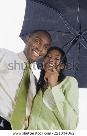 Hispanic couple standing under umbrella - stock photo