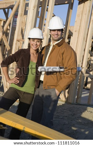 Hispanic couple with blueprint at construction site - stock photo