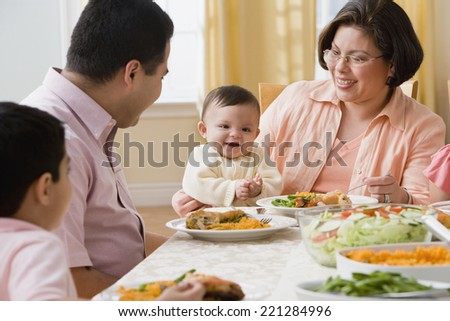 Hispanic family at dinner table - stock photo
