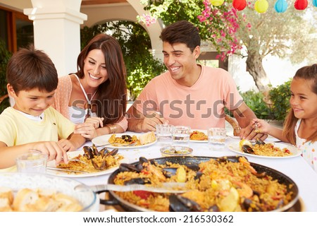 Hispanic Family Enjoying Outdoor Meal At Home Together - stock photo