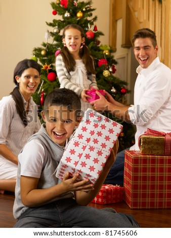 Hispanic family exchanging gifts at Christmas - stock photo
