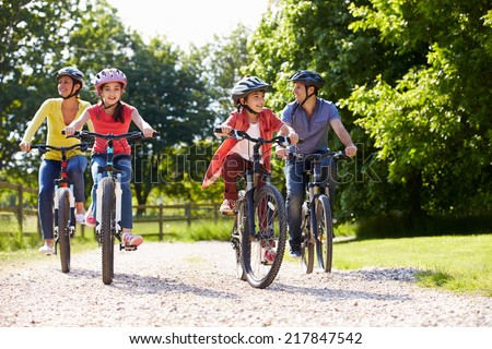Hispanic Family On Cycle Ride In Countryside - stock photo